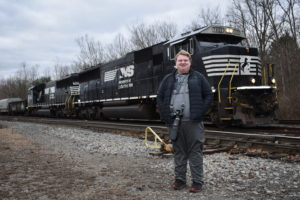 Eric Hudson stands along Norfolk Southern tracks as a train passes on the border of Sharon and Sharpsville.