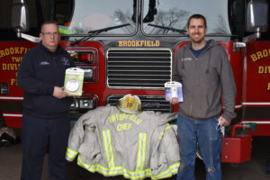 Brookfield Fire Capt. James Williamson, left, holds a smoke detector and T.J. Mohney of Mohney Heating and Cooling Inc., Masury, holds a carbon monoxide detector. The company donated 50 devices to the fire department to be distributed in the community. The donation honors former Fire Chief Keith Barrett, whose jacket is seen between them, and former Assistant Fire Chief Mark Christy, represented by the helmet.