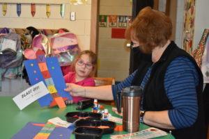 Brookfield United Methodist Church Preschool assistant teacher Linda Barnot holds the project student Vivian Vasconi put together.