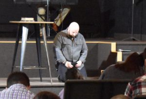 Jared Woodward kneels in prayer after delivering his last message as lead pastor of Six-Fourteen Church, Masury