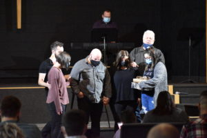 James Hunter, top right, offers a prayer for Pastor James Woodward, center, and Woodward's wife, Deanna, in black. The Woodwards founded Six-Fourteen Church but Jared Woodward has ended his service as lead pastor.