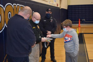Dilynn Turner explains his fire prevention poster to Ohio Fire Marshal Safety Educator Jesse Baughman. Brookfield Fire Chief David Masirovits is at left, and Fire Capt. Nick Cresanto at right.