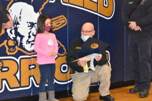 Ohio Fire Marshal Safety Educator Jesse Baughman shows Alivia Sanford the certificate she won for a poster submitted to a contest run by the marshal's office.