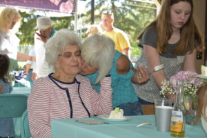 Barbara Gething gets a hug from her daughter-in-law, Angie, at a surprise 100th birthday party on May 1-NEWS On the Green photo.