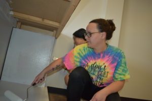 Megan May, with Dana Hughes behind her, paints the bar at Brookfield Nutrition.