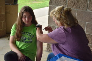 Tomi Liptak-Cardinale, a public health nurse with the Trumbull County Combined Health District, administers a COVID-19 vaccine to Madisyn Fisher of Brookfield.