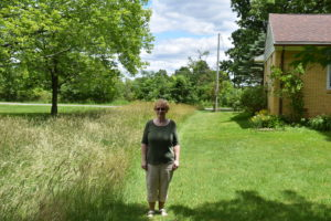 Kim Truhan stands in her yard on Sharon Hogue Road next to the high grass she has asked her neighbor to cut. The neighbor, Brookfield Tri-District Conservation Club, is noncommittal.