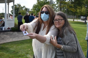 Rhonda Oliver, right, leans of her friend, Vicki S., as she releases a butterfly at an event sponsored by Trumbull County LOSS to remember those who died by suicide.