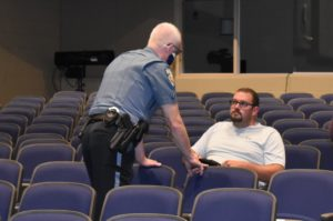 School Resource Officer Gerald Hockey asks Dominic Cinicola to conform with the Brookfield Local School District policy of wearing a mask on school property at a recent school board meeting. Cinicola complied.